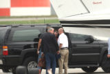 John Mark Karr (red shirt) is escorted off a Colorado State Highway Patrol aircraft by officers to...