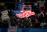 A fan of the U.S. Men's Mogul Team waves an American flag as U.S. skiier Travis Mayer takes to the...