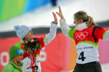 U.S. snowboarder and silver medalist Lindsey Jacobellis (L, #2) high fives Swiss snowboarder and...