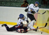 U.S. Women's Hockey Team member Caitlin Cahow (#8) gets tangled up in the corner with Finland's...