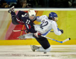 U.S. Women's Hockey Team member Natalie Darwitz (#22, blue) goes airborne after colliding with...