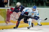 Team U.S.A.'s Erik Cole (#26) tries to sneak past the check of Team Finland's Saku Koivu (#11)...