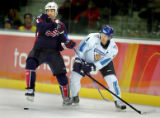 Team Finland's Kimmo Timonen (#4) grabs the stick of Team U.S.A.'s Brian Rolston (#12) as the two...