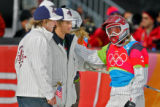 U.S. snowboarder Lindsey Jacobellis (far right) is consoled by teammates Nate Holland (far left)...