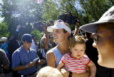 Susan Lavelle (cq, center) and her 10 month old daughter Madeleine (cq, in arms) take in the media...