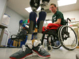 Tyler Carron, looks at his prosthesis at Spalding Rehabilitation Hospital. It was his first time...