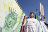 13-year-old Ben Duran holds one end of a banner featuring the Statue of Liberty as he and...