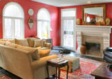 Deep red walls and plush rugs atop stained maple floors make this family room a popular spot for...