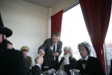 John F. Kennedy helps pay a restaurant bill with other members of the Presidents Day Society sit...