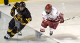 Colorado College defenseman Brian Connelly (11) and DU forward Anthony Maiani (16) skate for the...