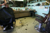 Fidel C. Hernandez, gets the final cuts from Douglas Dunbar. Dunbar's Holiday Barbershop, 933...