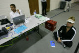 Voter Darlynn Daghlian waits on the floor in front of Election Judge Rose Jones, waiting for...