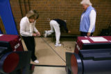 Election judges plug in voting machines in Centennial before polls open up in the gym of St....