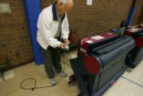 Election Judge Neil Knutson, prepares to  duct tape the electrical cord of a voting machine in...