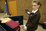 Election judge and voting machine specialist Joyce Knutson, left, notices that a seal for a voting...