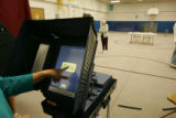 "Donna Bardallis, finishes up voting, using a new ""Edge"" touch-screen voting machine, at..."