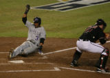 The Colorado Rockies' Willy Taveras slides in for a score in the top of the fifth inning of play...