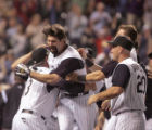 Colorado Rockies first basemen Todd Helton gets lifted up by his manager Clint Hurdle as he makes...