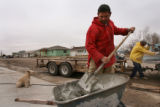 MJM459   Milton Hernandez (cq) mixes mortar as Brad Semmens (cq), right, cuts bricks as they...
