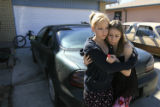 DM0016   Jennifer Gonser, 14, left, gets a hug from her friend Katarina Snider across the street...