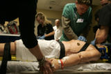University of Colorado President Bruce Benson watches senior nursing students try and save the...