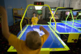 Parker Sukow, 8, of Aurora (cq) throws his hands in the air after losing his air hockey paddle and...