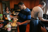 Branden, 15, (cq) squeezes out ranch dressing onto a sandwich he is helping make for dinner....