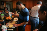 Branden, 15, (cq) squeezes ranch dressing onto a sandwich he is helping make for dinner. Germaine,...