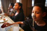 Joshua, 11, (cq) right,  Leslie, 15 (cq) center, and Germaine, 18 (cq) far left,  demonstrate how...