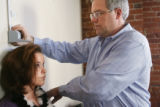 Brad Baldwin, Donna's son, measures the height of Lauren Songstad, who came to the office for an...