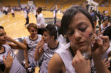 Cheerleader Hilda Barraza, 17 gets her face painted before Abraham Lincoln against Ralston Valley...