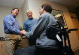 Mike Fordyce, left, talks with Henry Claypool, right, a patient from 1982, while Craig Hospital...