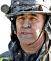 Denver firefighter Engineer Rich DeHerrera (cq) catches his breath after fighting a house fire at...
