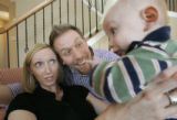 329 Shelley and Jason Martinkus enjoy the families new addition, Truman, 3 mo. as he wakes up from...
