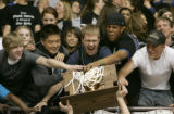 351 (5A) Highlands Ranch Falcons students reach out to touch the 5A championhip trophy asfter the...