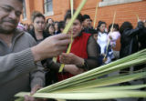 601 Parishioners pass out palm Leaves before a procession outside of the Church of the...