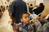 224 Joe Heliodora, 6, watche his sister make a cross out of a palm leaf during Palm Sunday Mass in...