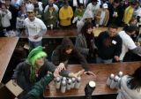 Beer servers jokingly fight for a glass of beer as dozens of thirsty athletes wait to be served at...