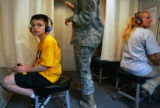 Ethan Moyer, 9, of Emporia, KS., left, gets a hearing test as he and his best friend Jake Smith,...