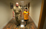 Senior Chief Wayne Cox walks with recruit Ethan Moyer, 9, of Emporia, KS., at the Military...