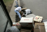 Kim DeNeir (cq) picks up items spilled from a box with her friend Bill Manning (cq) as they move...