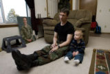 "DM0275   Master Sgt. Jeff ""J.T."" Theiral and his two-year-old son Jarret watch Elmo..."