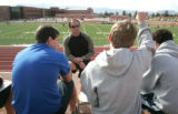 Nate Sassman quizzes students he is coaching quarterback class to, on plays, tafter school at...