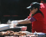Erica Sorenson (cq) prepares food for a stand operated by Old West BBQ  outside Coors Field early...