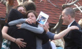 People hug after a memorial service and reception to honor the tragically shortened but touching...