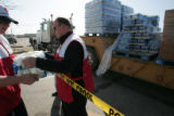 Red Cross volunteers unload water at a water distrubution center on Main St. in Alamosa Friday...