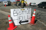 Volunteers set up  a water at a water distrubution center on Main St. in Alamosa Friday morning...