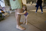 DM0091   Vienna Danna, 3, clings to her dad, Paul, as she kids around before going swimming at the...