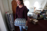 The Reverend Dawn Simpson, carries a case of water outside of the St. Thomas Episcopal Church  in...