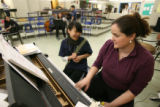 Lincoln High School music teacher Melissa Grundy plays the piano with student Amy Nguyen, 15, a...